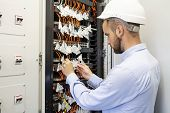 Technician Engineer Connects Optical Fibers Into Communication Switch In Data Center. Service Man In poster