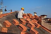 Construction Worker On A Roof Covering It With Tiles - Roof Renovation, Roofing Installation Of Tar  poster