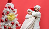 Happy Girlfriend Decorating Christmas Tree At Home With Boyfriend. Happy Family In Santa Hats Decora poster