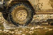 Off Road Sport Truck Between Mountains Landscape. Bottom View To Big Offroad Car Wheel On Country Ro poster