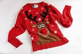 Christmas Sweater With Pattern On Wooden Background, Top View poster