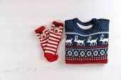 Christmas Sweater And Socks With Pattern On Wooden Background, Top View poster