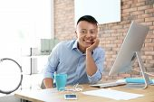 Happy Young Businessman Enjoying Peaceful Moment At Workplace poster