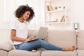 African-american Woman Working On Laptop Computer, Sitting On Sofa At Home, Copy Space poster