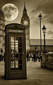 stock photo of big-ben  - Sepia image of The Big Ben in London with a bright full moon and a phone booth in the foreground - JPG