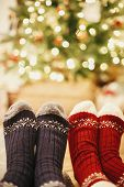 Stylish Festive Socks On Couple Legs On Background Of Golden Beautiful Christmas Tree With Lights In poster