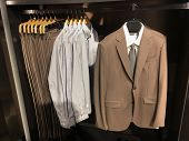 Men clothes row of clothes, suit, jacket, pants on the racks in clothing store  poster