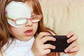 Childhood, Childcare, Being Polite Concept. Little Toddler Girl With Bandage On Eye Playing Games On poster