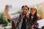 Couple Sitting On Concrete Ledge Taking Selfie. Young Man And Attractive Woman With Backpacks Sittin poster