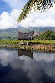 stock photo of minangkabau  - Water and house SAmosir island Toba Sumatra - JPG