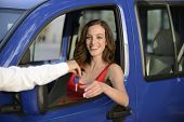 happy woman receiving keys of her new car from dealer