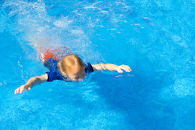 pic of wet pants  - Young boy learning to swim with his clothes on in a pool - JPG