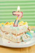 stock photo of birthday-cake  - slice of seventh birthday cake with lit candle confetti and ribbon  - JPG