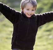 picture of character traits  - Young boy smiling and running with arms outstretched outdoors - JPG