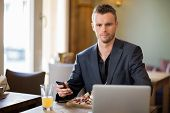 Portrait of confident young businessman with mobilephone and laptop sitting in coffeeshop