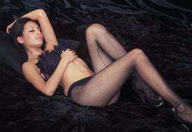 foto of fishnet stockings  - Beautiful actress model in fishnet stockings lying on bed - JPG