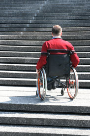 stock photo of crippled  - a man is sitting in a wheelchair - JPG