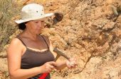 pic of paleontologist  - Senior woman geologist tap a rock formation with a hammer - JPG
