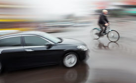 picture of dangerous situation  - Dangerous city traffic situation with a cyclist and cars in motion blur - JPG