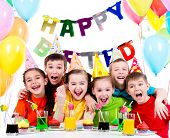 stock photo of birthday hat  - Group of laughing kids having fun at the birthday party  - JPG