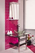 image of bathroom sink  - detail of a modern bathroom interior in pink and white with sink of glass - JPG