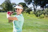 picture of take off clothes  - Female golfer taking a shot and smiling at camera on a sunny day at the golf course - JPG