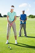 pic of ladies golf  - Lady golfer teeing off for the day watched by partner on a sunny day at the golf course - JPG
