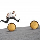 picture of barrel racing  - Concept of difficulty with businessman that jumps obstacles - JPG