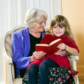 pic of babysitting  - Grandma Reading to Her Grand Daughter as she sits on her lap - JPG