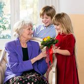 stock photo of grandmother  - Children giving grandmother flowers as a gift - JPG