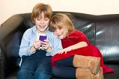 picture of snuggle  - Two young children playing with a mobile phone as they snuggle together on a sofa with the brother laughing at the message on the screen watched by his cute smiling sister - JPG