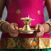 stock photo of deepavali  - Diwali or deepavali photo with female hands holding oil lamp during festival of light - JPG