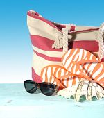 stock photo of blue things  - Summer vacation holiday gear with red and white strip beach bag flip flop things shell and sun glasses on a aqua blue table against a blue sunny sky - JPG