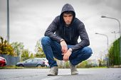 stock photo of single man  - Attractive young man with hoodie and baseball cap in city street looking at camera - JPG