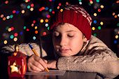 stock photo of letters to santa claus  - The child writes a letter to Santa Claus - JPG