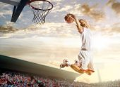 foto of slam  - Basketball player in action on background of sky and crowd - JPG