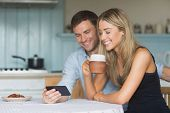 image of hot couple  - Cute couple using smartphone together at home in the kitchen - JPG