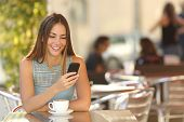 foto of restaurant  - Girl texting on the smart phone in a restaurant terrace with an unfocused background - JPG