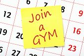 picture of joining  - A resolution to Join a Gym written on a yellow sticky note attached to a wall calendar - JPG