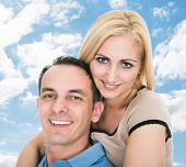 image of piggyback ride  - Portrait of happy mid adult man giving piggyback ride to woman against sky - JPG