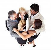 stock photo of huddle  - High angle view of multiethnic business people forming huddle over white background - JPG