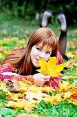 pic of gril  - redheaded gril lating on the meadow in autumn forest - JPG