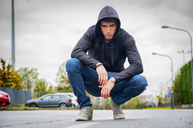 pic of hoodie  - Attractive young man with hoodie and baseball cap in city street looking at camera - JPG