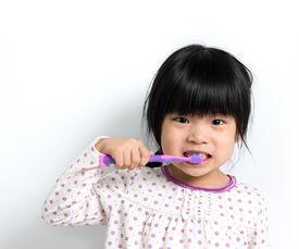 stock photo of pyjama  - Little Asian girl in pyjamas brushing teeth - JPG