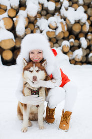 stock photo of laika  - Cute girl hugging her friend the dog Laika on the background of the forest in the winter - JPG