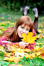 stock photo of grils  - redheaded gril lating on the meadow in autumn forest - JPG
