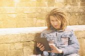 pic of dreadlocks  - freelancer guy with dreadlocks sitting on staircase with digital tablet typing message warm filter applied - JPG