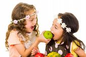 stock photo of healthy eating girl  - Beautiful healthy little girls eating delicious fresh fruits isolated on white - JPG
