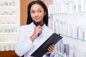 stock photo of toothless smile  - Thoughtful young African woman in lab coat holding clipboard and looking away with smile while standing near the shelf in drugstore - JPG