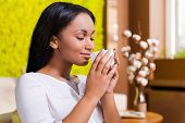 picture of toothless smile  - Side view of beautiful young African woman holding coffee cup near nose and smiling while keeping eyes closed and sitting at the chair at home - JPG